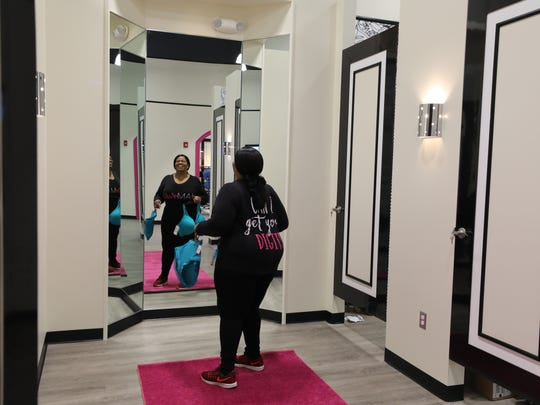 Aretha Blake of Harlem, a buyer with Ashley Stewart looks in the mirror in the plush fitting area that is classically decorated at their new store that is opening in Newark.