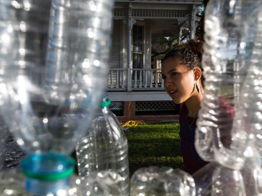 Melissa Zamora looks over the first string of water bottles hung from a tree as the Epic Plastic Project is constructed in Heritage Park before Earth Day-Bay Day on Saturday, April 8, 2017.