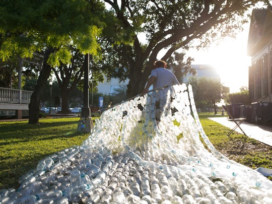 John Meza pulls a panel of water bottles as he helps construct the Epic Plastic Project in Heritage Park before the start of Earth Day-Bay Day on Saturday, April 8, 2017.
