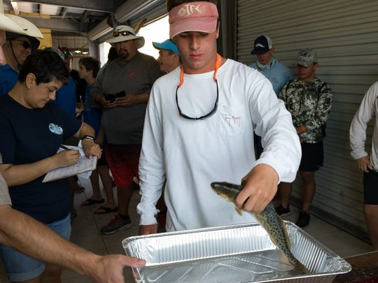 Tyler Johnson, a Ray High School student and founder of the school's Texan Anglers fishing club, presents a fish to be weighed during the 2017 Hooked On Big Brothers Big Sisters Fishing Tournament at the Bluff's Landing Marina on Saturday, April 8, 2017.