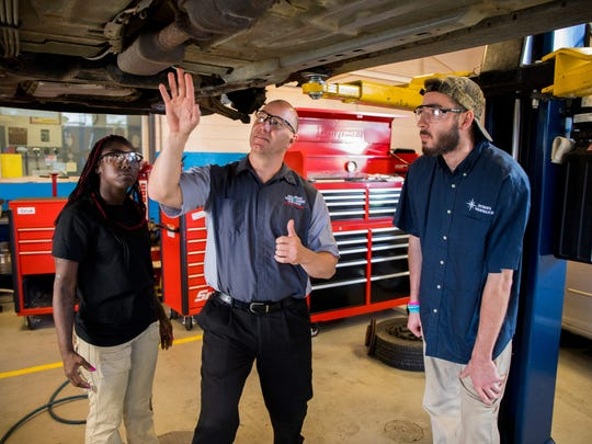 Automotive instructor Kyle Quillen (center), with students Kimberly Brown and Scott Wallen, performs an undercarriage inspection on a car at Delaware Technical Community College's Georgetown campus.