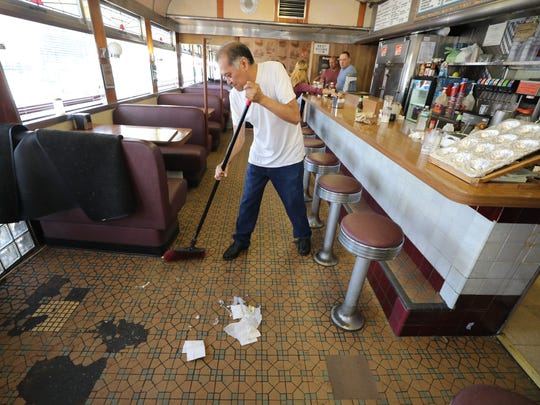 Salvador Suarez cleans up after the final lunchtime at the Egg Platter Diner in Paterson, an institution on Crooks Avenue that the Dermatis family has owned since 1977.