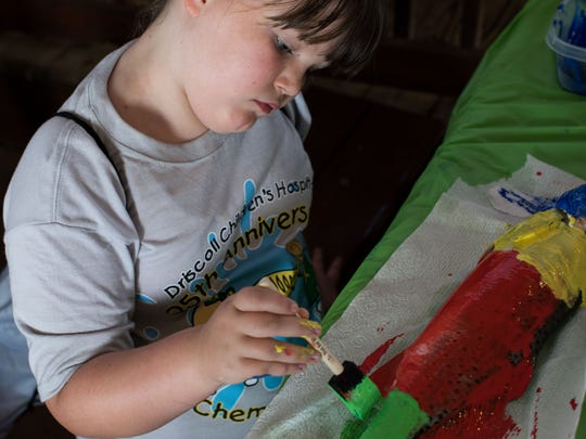 Makenna Wickliffe paints a fish to make a print during Driscoll Children's Hospital's 25th annual Chemo Kids Fish Off in Aransas Pass on Tuesday, June 6, 2017