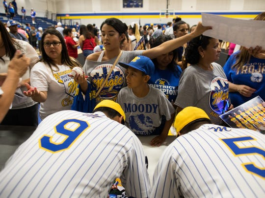 The Moody baseball team signs posters for fans during a pep rally before the team heads to the state tournament, Tuesday, June 6, 2017.