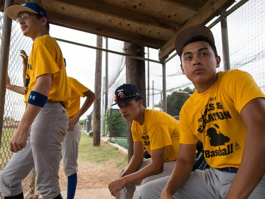 The Trojans watch as a teammate bats during the 2017 High School Baseball League week 16 and under junior/ freshman mix division championship game at Carroll High SchoolÊon Thursday, July 13, 2016.