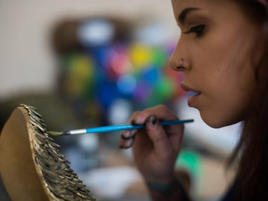 Cosplayer Rozlin Gomez known as Rozzmonster sits in the grudge of her home painting the armer of her Aquaman costume for the upcoming Corpus Christi Comic Con.