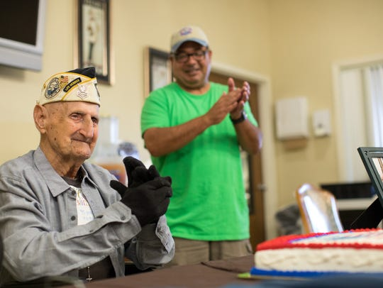 Pearl Harbor survivor Harry Ogg sits infant of birthday