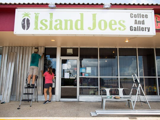 Bryan and Brenda Tumlinson install storm shutters on their store, Island Joe's Coffee and Gallery, on North Padre Island in Corpus Christi ahead of Hurricane Harvey on Thursday, Aug. 24, 2017.