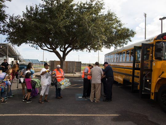 Residents broad a bus at the Corpus Christi Natatorium