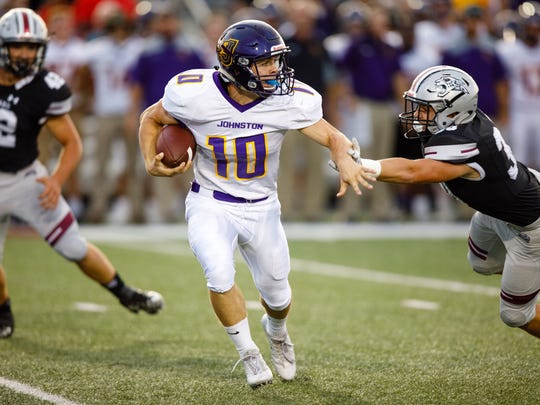 Johnston High School's Andrew Nord (10) runs the ball as Ankeny Centennial's Brandon VanMeter (30) tries to tackle him in the first half Friday, Aug. 25, 2017, during their game in Ankeny.