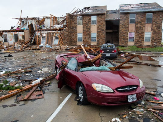 A car crushed by hurricane debris rests outside the heavily damaged Saltgrass Landing apartment complex in Rockport.