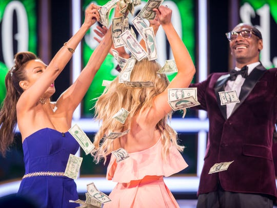 Snoop Dogg and Lady Luck Jeannie Mai, left, show a winning contestant the money on TBS' 'Snoop Dogg Presents The Joker's Wild.'