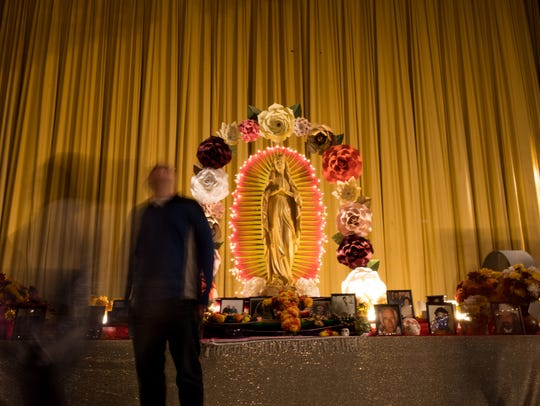 People walk past the main altar in the Ritz Theater during the 10th annual Dia de los Muertos Street festival in downtown Corpus Christi on Saturday, Oct. 28, 2017.
