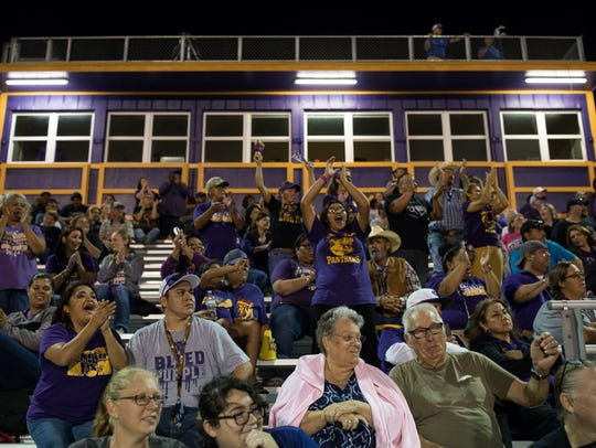 Fans in the stands cheer during Aransas Pass's homecoming