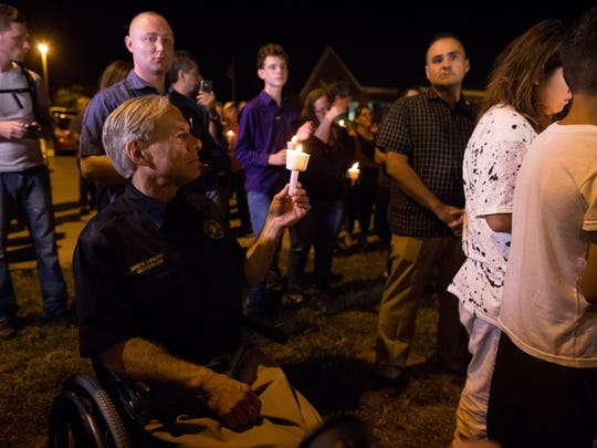 Gov. Greg Abbott holds a candle during a vigil kept across the street from the First Baptist Church of Sutherland Springs where 26 people were killed in shooting Sunday, Nov. 5, 2017, in Sutherland Springs.