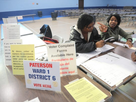 Poll workers Calandra Matthews and Melisa Morgan help voters sign in at the St. Joseph's Community Center in  Paterson.