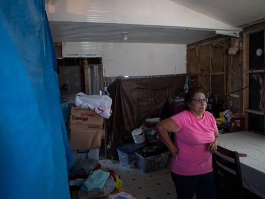 Norma Navarro stands in her kitchen, which was badly damaged by Hurricane Harvey. Her family has been using tarps to divide the rooms of the house after sheetrock removal left the walls bare.