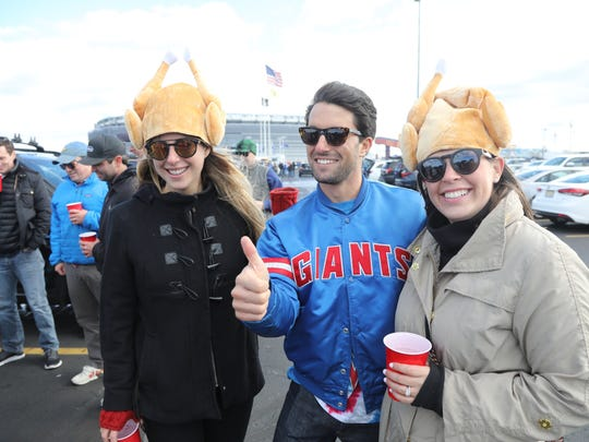 Amelia Johnson of Darien, Conn., with Giants fan Rick Sander of Manhattan and fellow turkey hat participant Leslie Moore of Chevy Chase, Md., outside MetLife Stadium on Sunday. Sander, a Giants fan, doesn't blame management for the team's poor season.