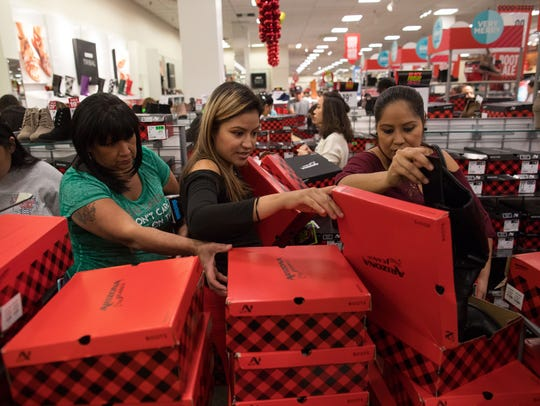 Women look through boxes of boots at JCPenney shortly