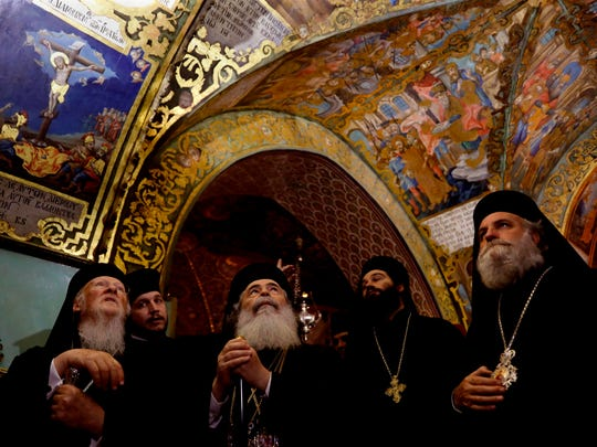 Greek Orthodox Patriarch of Jerusalem Theophilos III, second from left, and Ecumenical Patriarch of Constantinople Bartholomew, I, left, look at the painting of the Golgotha at the Church of the Holy Sepulchre in Jerusalem's Old City on Dec. 5, 2017.