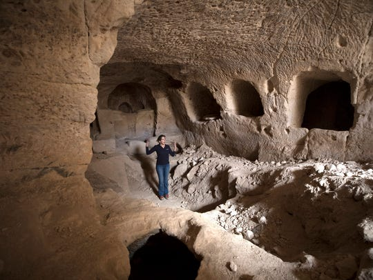 An Israel Antiquities Authority employee, Michal Haber, shows a cave from the Hasmonean period found next to a 2200-year-old structure from the Hellenistic period, possibly an Idumean palace or temple.