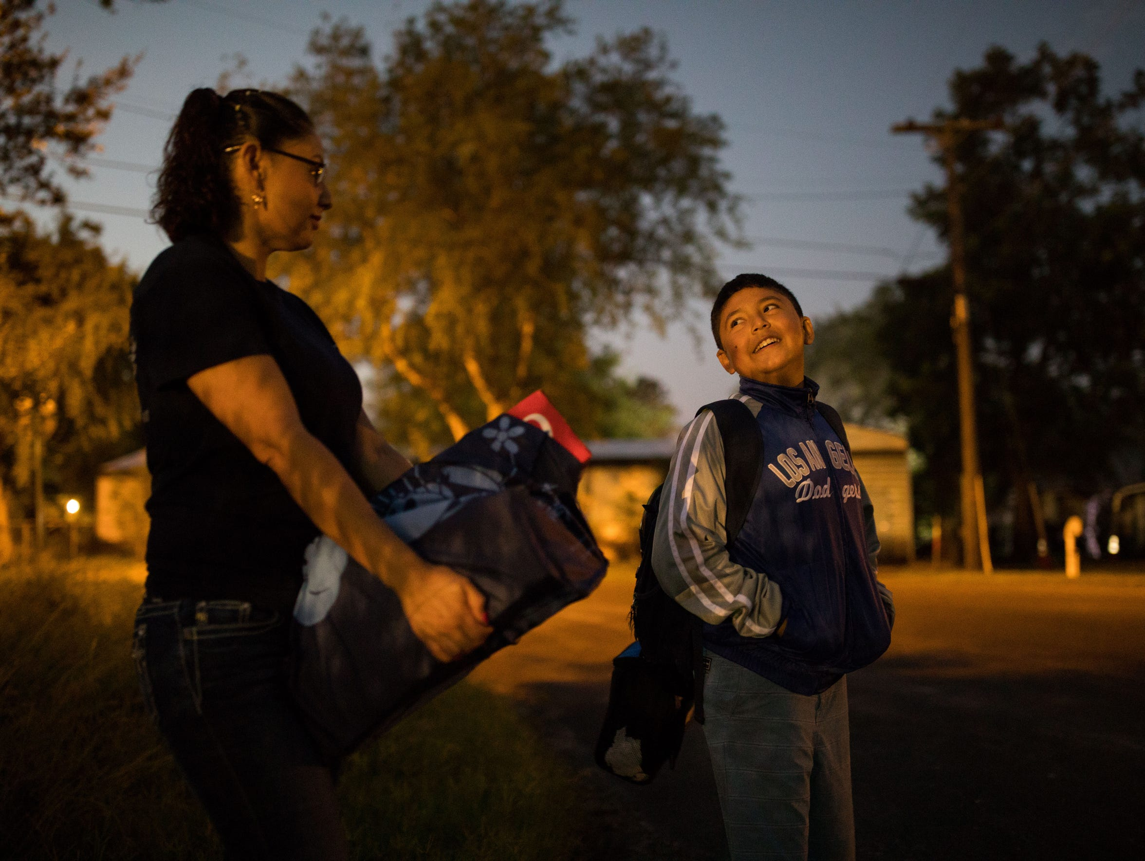 Monica Rocha Alcarez holds sodas for her 10-year-old son Hector Palacios class as they wait at his bus stop on Sept. 29, 2017. Rocha Alcarez, who was brought over from Mexico at the age of four, is a DACA recipient. She's since graduated with a business degree and owns her own business.