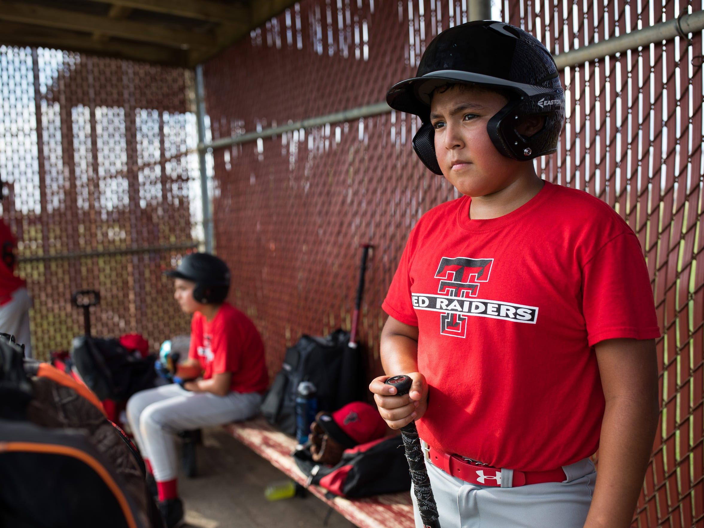Monica Rocha's youngest son 10-year-old Hector Palacios stands in the dugout during a baseball game at Lyondell park on Sunday, Oct. 15, 2017.