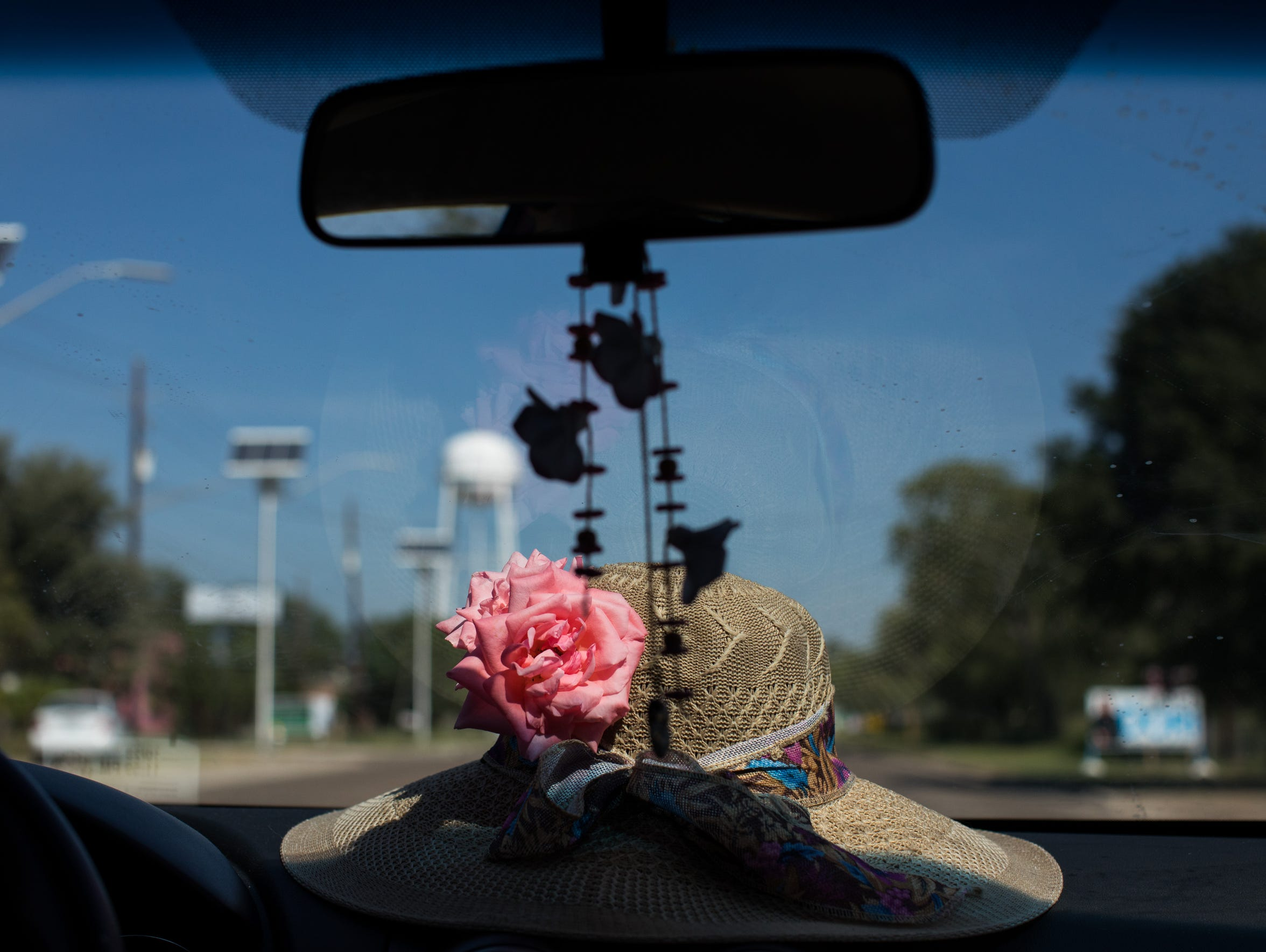 A flower sits on a hat in the front window of Maria