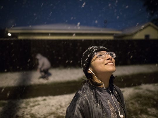 Thirteen-year-old Eva Cantu sees her first snow fall standing on Kostoryz Road looks up to the sky in Corpus Christi on Friday, Dec. 8,2017.