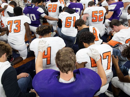 Refugio and Mason players kneel for a prayer following