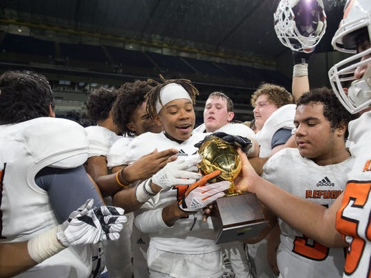 Refugio players hold a trophy following the teams 38-14