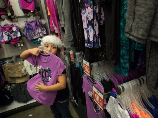 Seven-year-old Aaliyah Felan holds a shirt up to her
