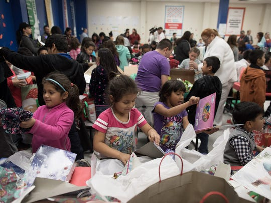 Students unwrap presents during Crockett Elementary's second annual Christmas Tree Angel event on Wednesday, Dec. 13, 2017.