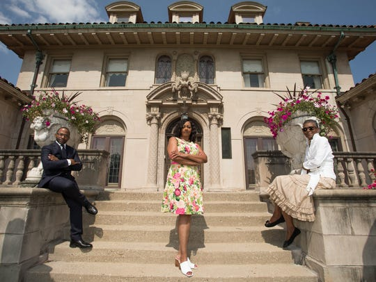 Detroit real estate agents Jason Hill, left, Deborah Smith, center and Betty Warmack, right, stand before the Motown Mansion in Detroit.