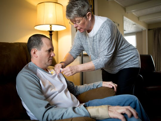 Ann Spears gives her son-in-law, Paul Rinderknecht, a dose of edaravone in 2018 for the treatment of ALS. Edaravone had been used in Japan since 2015, but was only FDA-approved in May 2017, making it only the second drug on the U.S. market to treat the disease