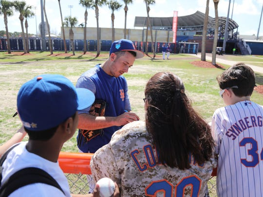 Mets workout this afternoon. TJ Rivera signs autographs on his way to the locker room after practice.