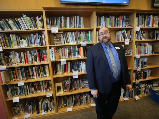 Peter Coyl is the Director of the Montclair Library where he stands in front of shelves of books that were borrowed from other BCCLS libraries and not yet returned.