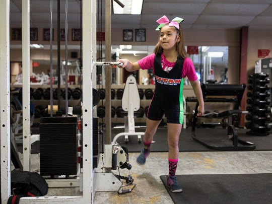Powerlifter Celeste Godinez, 9, stretches before her workout Wednesday, Feb. 28, 2018, at Ironhouse Gym in Beeville.