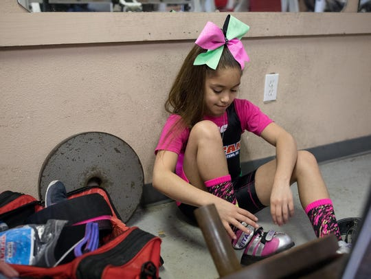 Powerlifter Celeste Godinez, 9, puts on her lifting