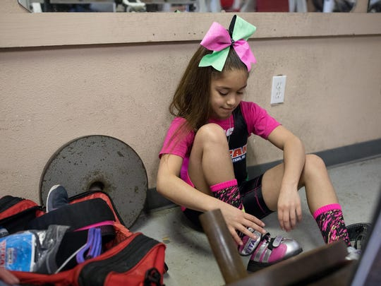 Powerlifter Celeste Godinez, 9, puts on her lifting shoes before her workout Wednesday, Feb. 28, 2018, at Ironhouse Gym in Beeville.