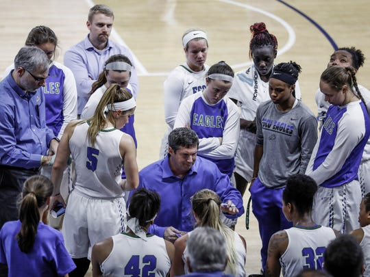 FGCU players huddle around head coach, Karl Smesko during a timeout against NJIT at Alico Arena on Friday, March 2, 2018.
