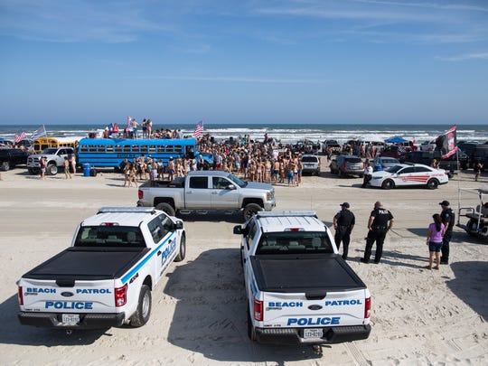 Port Aransas police watch over a large crowd of people on the beach in Port Aransas during the first day of spring break on Saturday, March 10, 2018.