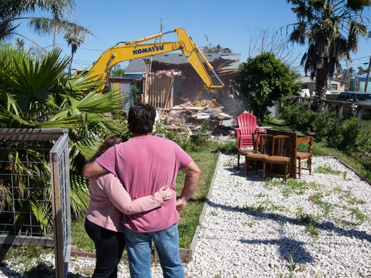 Tom Gomez holds his wife as they watch the demolition of their Port Aransas home, badly damaged by Hurricane Harvey. The couple plans to rebuild, but it is unclear how many other residents will do the same.
