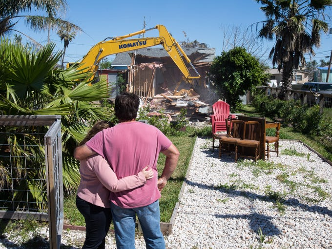 Tom Gomez holds his wife as they watch the demolition