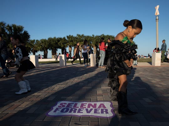 A young girl dressed as Selena walks past a Selena Forever marker at  Fiesta de La Flor on Saturday, April 14, 2018.