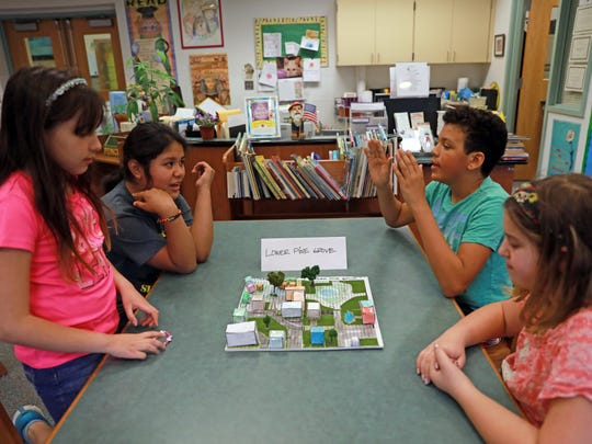 From left, Adena Velasquez, 10, Alison Gonzalez, 11, Miles Peters, 11, and Lily Alinkossky, 11 discuss their winning project where they were tasked to redesign downtown Sloatsburg using urban planning principles at Sloatsburg Elementary on May 9, 2018.