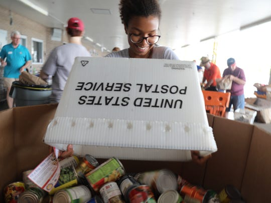 A volunteer at Fort Myers' Page Field post office helps unload and sort mountains of food collected by local carriers Saturday as part of the 26th annual National Association of Letter Carriers food drive.