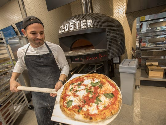 the wood fired pizza oven spews out pizza at Whole