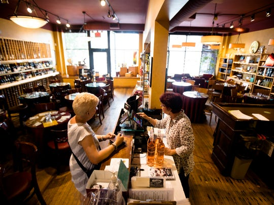 Kate Weldishofer, right, co-owner of Marty's Hops & Vines, sells wine to a customer at Marty's Hops & Vines on Tuesday, June 12, 2018, in College Hill.