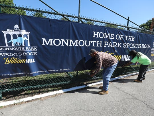 Carpenters at Monmouth Park Noel Robinson and Jagod Davis attach a sign on the fence air the entrance of Monmouth Park announcing the opening of sports betting in New Jersey.